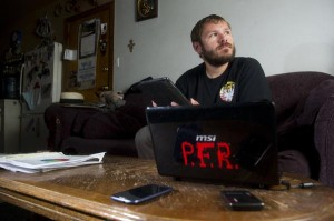 Victor Head sits in his Pueblo home Tuesday, surrounded by the phone, laptop and tablet he used to gather signatures for a recall petition. Head used the technology to access voter registration information available online.